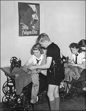 "Inside a sewing room of the BDM in 1942 as Hitler Youth uniforms are brought in to be mended. On the wall hangs a portrait of Hitler saying: ""We follow Thee."""