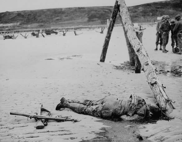Crossed rifles in the sand placed as a tribute to this fallen soldier